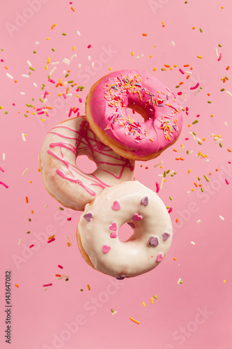 Various decorated doughnuts in motion falling on pink background.