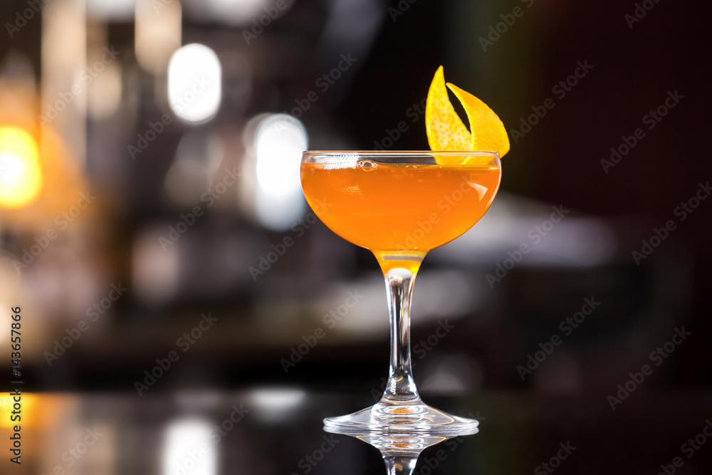 Fototapeta Glass of sidecar orange cocktail decorated with lemon at bar counter background.