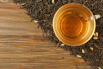 FototapetaDried tea leaves and cup of aromatic drink on wooden background