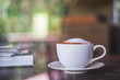 A white cup of coffee on wood table