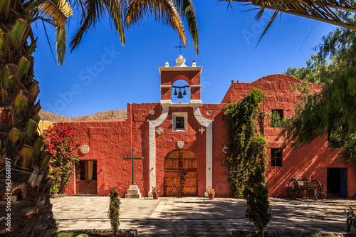 Red walls of Spanish catholic chapel with palms, trees and flowers, Arequipa, Pe Canvas Print