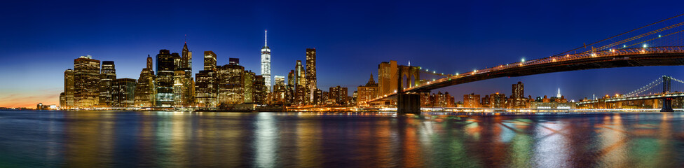 Panoramic view of Lower Manhattan Financial District skyscrapers at twilight with the Brooklyn Bridge. New York City