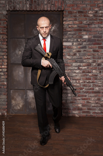 Photo  Assassin in suit and red tie holding machine gun
