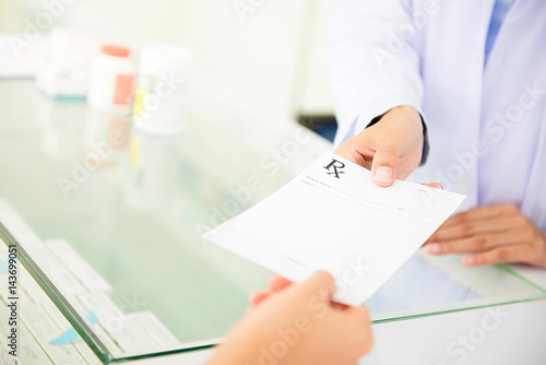 Customer (patient) giving prescription to pharmacist Canvas Print