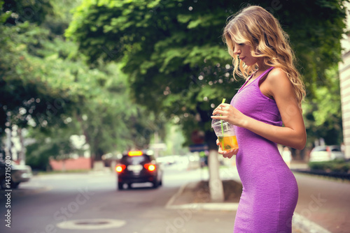 Fotografía  Sexy woman in purple dress drinking Ice Tea outdoors.