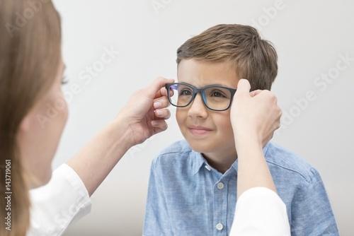 Female optician putting glasses on boy