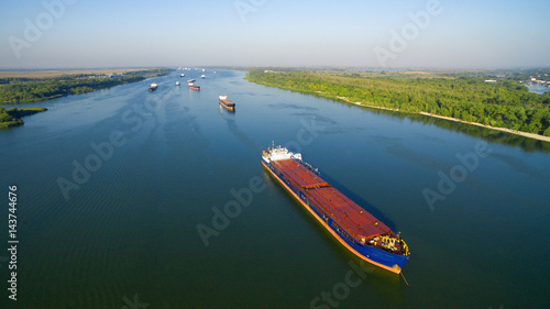 Fotografia  Caravan of barges on the river