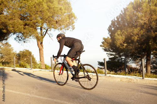 Sideways view of male cyclist wearing black clothes and protective