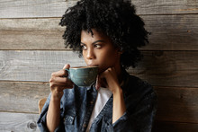 Attractive Afro American Hipster Girl Dressed Stylishly Drinking Coffee Or Tea Thoughtfully Out Of Big Cup, Looking Away With Serious Pensive Expression, Making Plans For Day. People And Lifestyle