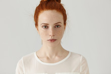 Pretty Student Girl With Ginger Hair In Knot Relaxing At Home After College. Headshot Of Tender Charming Young Woman With Freckles Wearing White Blouse Posing At Studio Wall, Having Calm Expression