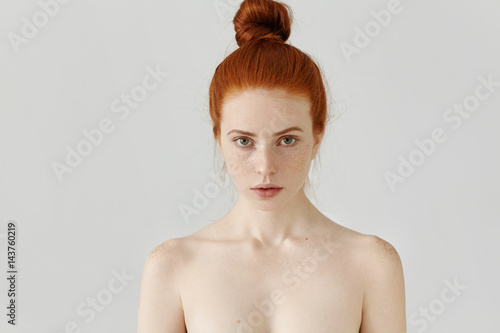 Fotografia  Isolated portrait of beautiful young Caucasian redhead woman with hair bun and p