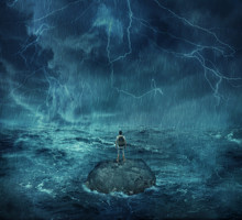 Lost Man Standing Abandoned On A Rock Island In Middle Of The Ocean, In A Stormy Night With Lightnings In The Sky. Looking For Help, Try To Survive. Adventure, Journey And Hard Determination Concept.