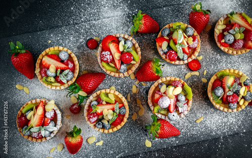 Fényképezés  Berry tartlets with blueberries, raspberries, kiwi, strawberries, almond flakes in icing sugar