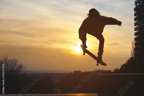 Платно The teenager in a sweatshirt and a cap jumps with a board in the city against the backdrop of the urban sunset