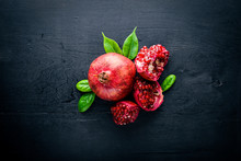 Fresh Pomegranate On A Dark Wooden Surface. Top View.