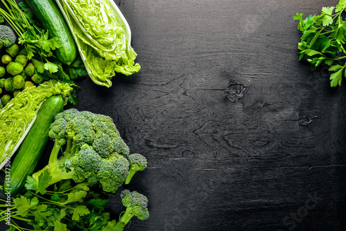 Stampe  Collection of fresh green vegetables placed on black stone