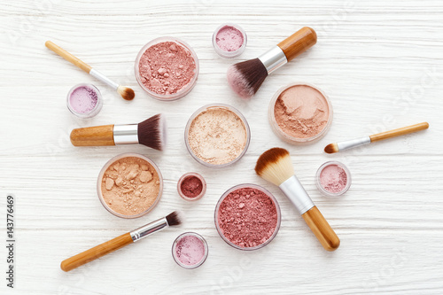Photo  Makeup powder products with brushes flat lay