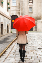 Back View Of Woman With Red Umbrella Walking In The Old Town.
