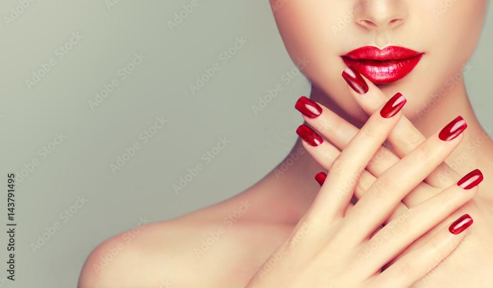 Fototapeta Beautiful girl showing red  manicure nails . makeup and cosmetics