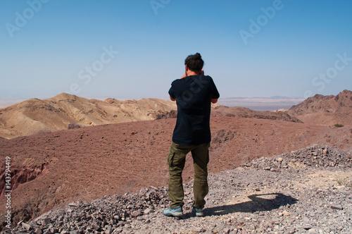Tuinposter Midden Oosten Medio Oriente, 10/03/2013: un uomo di spalle fotografa il paesaggio deserto sulla strada che collega la Riserva Biosfera di Dana, la più grande riserva naturale della Giordania, a Petra