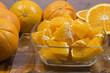 Naranjas troceadas en una fuente de cristal transparente, naranjas enteras sobre la mesa