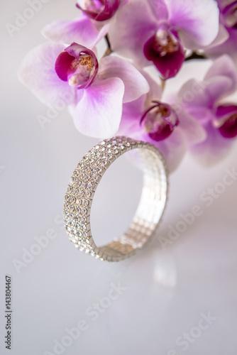 Zirconium bracelet lies on the background of purple orchids Canvas-taulu