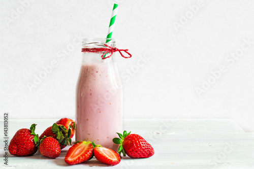 Staande foto Milkshake Strawberry smoothie or milkshake in a bottle with straw