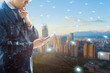 Double exposure of professional businessman connected internet and wireless network with his smart phone and city of business background in business trading and technology concept