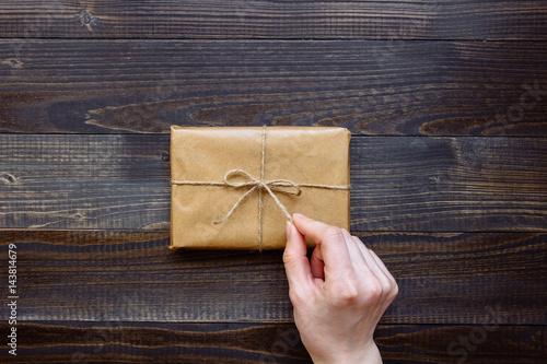 Plakat kobiece strony rozpakowaniu pudełko zapakowane z papieru rzemiosła i kwiaty na drewniany blat Zobacz. Prezent na wakacje