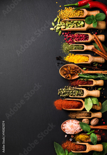 Background with various spices on black slate. Top view Canvas Print