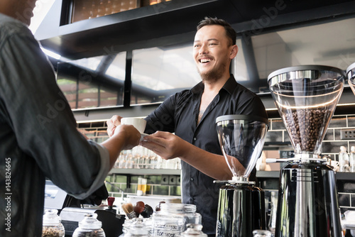 Fotografía  Friendly bartender serving espresso coffee to a customer in a modern coffee shop
