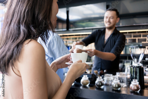 Fotomural Young woman holding a white cup of coffee next to her partner in a modern coffee
