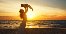 Happy Family Mother With Baby Son Walks By Ocean On Beach In Summer