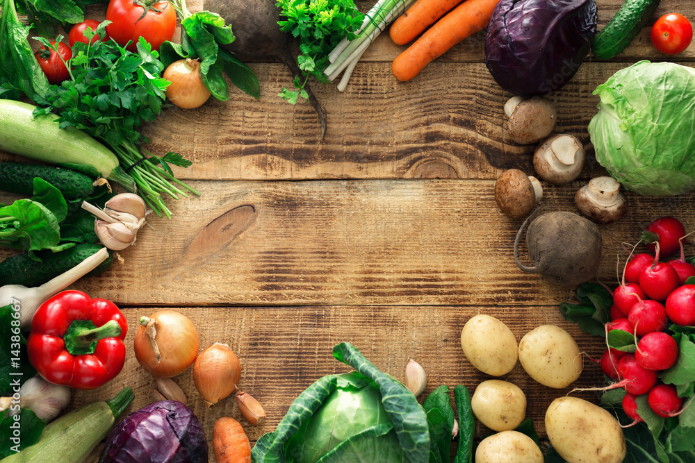 Frame of different vegetables on a wooden table