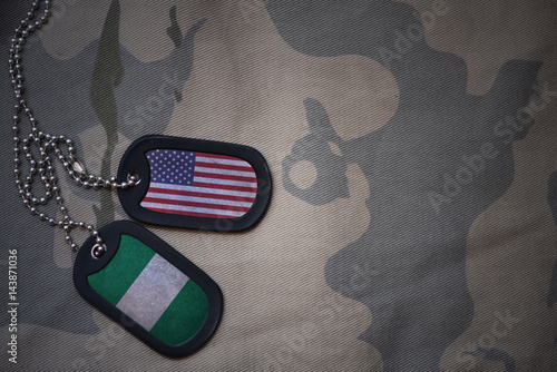 army blank, dog tag with flag of united states of america and nigeria on the khaki texture background Fototapet