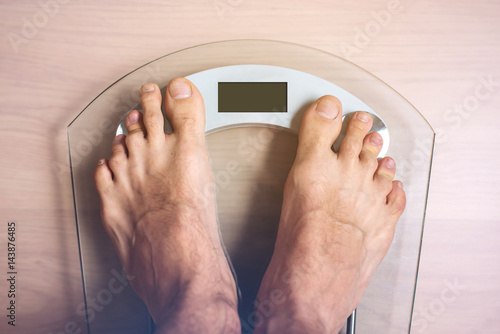 Male Feet Standing On Electronic Scales For Weight Control