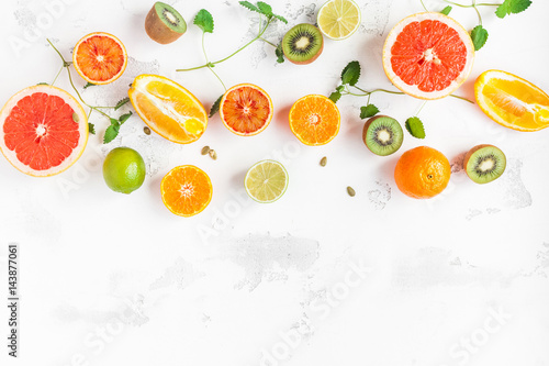 Foto op Aluminium Vruchten Fruit background. Colorful fresh fruit on white table. Orange, tangerine, lime, kiwi, grapefruit. Flat lay, top view, copy space