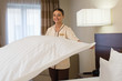 Hotel housekeeper making bed in hotel room.