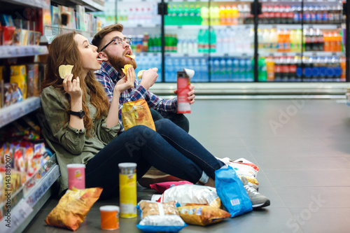 Valokuva  Couple sitting on the supermarket floor and eating snacks