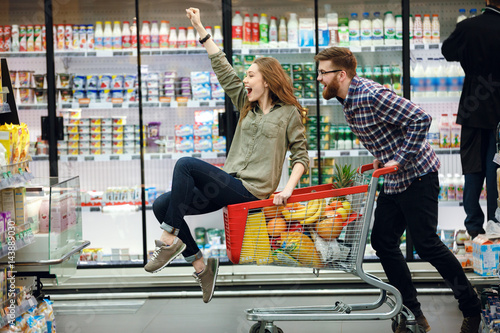 Beautiful couple having fun while choosing food in the supermarket
