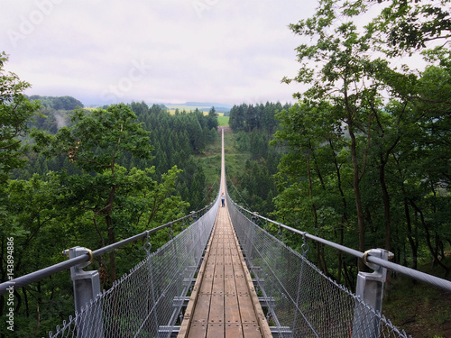 Fotografía  Geierlay suspension bridge from south to north with a man taking pictures