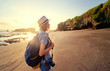 Tourism and photography. Young traveling woman with camera and rucksack walking by sea beach.
