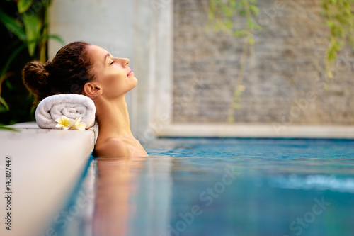 fototapeta na szkło Beauty and body care. Sensual young woman relaxing in outdoor spa swimming pool.