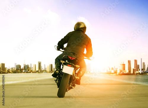 Plakat widok z tyłu człowieka jazdy motocyklem na drodze ruchu miejskiego dla osób rozrywki podróży tematu