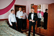 Groom wears on his room at morning wedding with best mans.