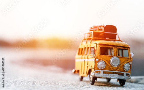 Miniature yellow van on the long road with summer scene