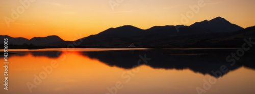Tuinposter Baksteen Colorful sunset over lake and mountains