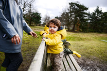 Baby Boy With Mother In Yellow Anorak On Park Bench