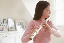 Girl Practicing Flute In Livin...