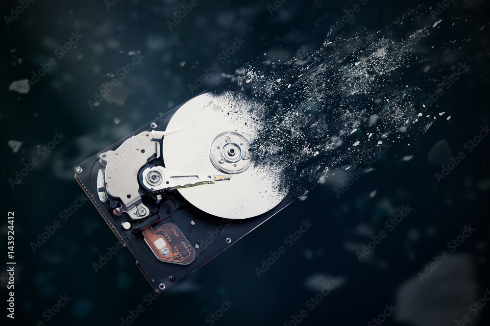 Fototapeta The old hard disk drive is disintegrating in space. Conception of passage of time and obsolete technology